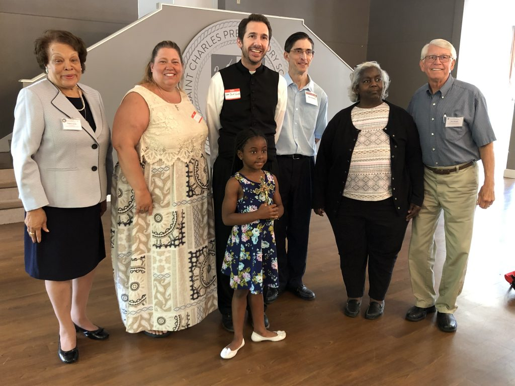 Pictured left to right Virginia Hardy, Laura Miller, Father David Schalk, Gino Dimattia, Liz Carle, Tom Murphy and holding the Crucifix Iyonna Godfrey